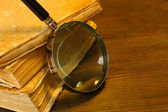 Magnifying glass and books on table — Foto Stock