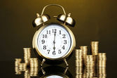 Alarm clock with coins on dark background — Stock Photo
