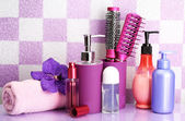 Hair brushes and cosmetic bottles in bathroom — Stock Photo