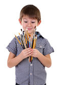 Cute little boy with paintbrushes isolated on white — Stock Photo