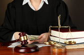 Judge sitting at table during court hearings on black background — Stock Photo