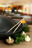 Black wok pan and vegetables on kitchen wooden table, close up — Stock Photo