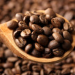 Coffee beans in wooden spoon, close up - Stock Photo