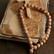 Bible, rosary and cross on wooden table close-up - Stock Photo