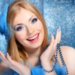Stock Photo: Portrait of beautiful young woman with glamour make up, on blue background
