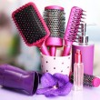 Hair brushes, hairdryer and cosmetic bottles in beauty salon -  