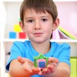 Cute little boy holding hand-made plasticine hourse over desk — Stock Photo