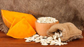 Pumpkin seeds in sack, on wooden background — 图库照片