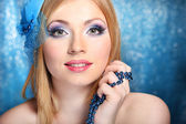 Portrait of beautiful young woman with glamour make up, on blue background — Foto Stock