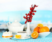 Beautiful white dinner service with oranges on blue tablecloth on natural background — Stock Photo