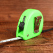 Tape measure on wooden background - Stock Photo