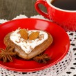 Chocolate cookie in form of heart with cup of coffee on wooden table close-up - Stock Photo