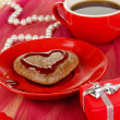 Chocolate cookie in form of heart with cup of coffee on pink tablecloth close-up - Stock Photo
