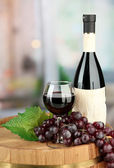 Composition of wine bottle, glass and grape,on wooden barrel, on bright background — Stock Photo