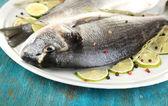 2 魚のドラド ブルー木製テーブルのクローズ アップにプレート上のレモン — ストック写真