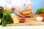 Female hands preparing cheeseburger, on blue background — Foto Stock