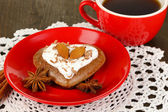 Chocolate cookie in form of heart with cup of coffee on wooden table close-up — Photo