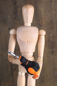 Mannequin with screwdriver, on grey wooden background — Stock Photo