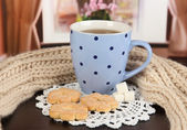 Cup of tea with scarf on table in room — Stock Photo