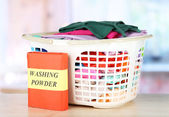 Clothes in plastic basket on table in room — Stock Photo