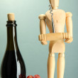 Mannequin with corkscrew and wine bottle, on grey background — Stock Photo