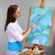 Beautiful young woman painter at work, on grey background — Stock Photo