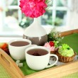 Cups of tea with flower and cakes on wooden tray on table in room — Stock Photo