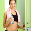 Young girl in locker room with towel and bottle of water — Stock Photo #20405447