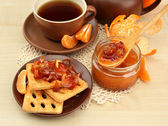 Light breakfast with tea and homemade jam, on wooden table — Stock Photo