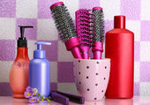 Hair brushes, hair straighteners and cosmetic bottles in bathroom — Stock Photo
