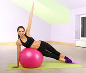 Young woman with gym ball at gymnasium — Stock Photo