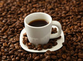 Cup of coffee on coffee beans background — Stock Photo