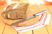 Sliced bread with sesame seeds and knife on chopping board on wooden table close up — Stock Photo