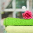Stock Photo: Stack of towels with fragrant flower on window background