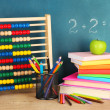 Toy abacus, books and pencils on table, on school desk background — Stockfoto