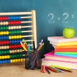 Toy abacus, books and pencils on table, on school desk background — ストック写真