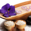 Spa stones and wooden bowl with candles and purple flower, on wet background — Stock Photo