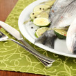 Two fish dorado with lemon on plate on wooden table close-up - Stock Photo