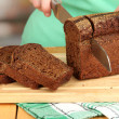 Woman slicing black bread on chopping board on wooden table close up — Stock Photo