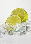 Ice cubes with lime isolated on white — Stock Photo