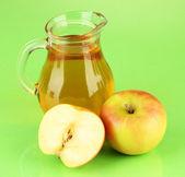 Jarro lleno de jugo de manzana y manzana sobre fondo de color — Foto de Stock