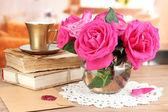 Belles roses roses dans un vase sur une table en bois sur le fond de la salle — Photo