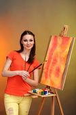 Pittore giovane e bella donna al lavoro, su sfondo di colore luminoso — Foto Stock