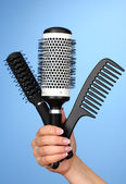 Three combs in female hand on color background — Photo