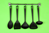Black kitchen utensils on silver hooks, on green background — Stock Photo