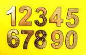 Golden numbers with drops, on yellow background — Stock Photo