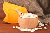 Pumpkin seeds in wooden bowl, on sackcloth background — Stock Photo