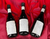 Wine bottles on red cloth background — Stock Photo