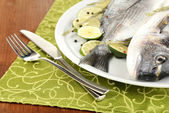 Two fish dorado with lemon on plate on wooden table close-up — Stockfoto