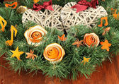 Corona di natale decorato con rosa dalla buccia di arancia secca sul tavolo di legno — Foto Stock